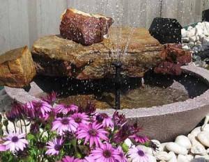 маленький водоем с фонтаном в саду