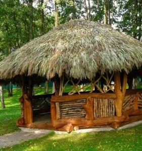 красивая дачная беседка в стиле рустик из бревен, плетня и соломенной крыши