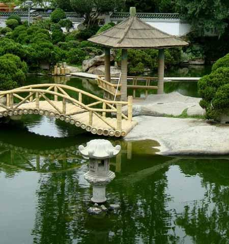 красивая беседка на берегу пруда в саду