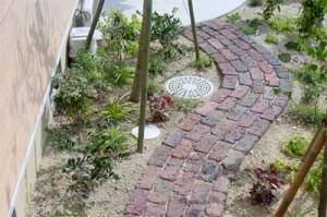 изогнутая садовая дорожка с укладкой из кирпича